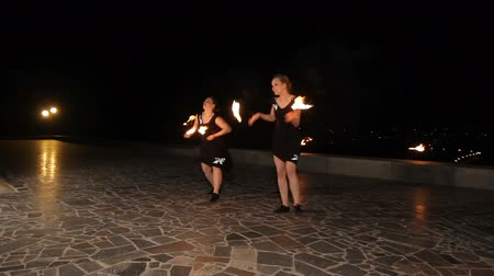 зажигание : Women twist fiery circles on a fire show.Women does a fire performance.Fire show amazing at night.
