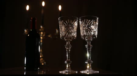 şarap kadehi : Wine glasses on the table, a bottle of red wine and burning candles in a beautiful chandelier behind on a black background.Romantic atmosphere with wine glasses and candles.Video footage on the move.