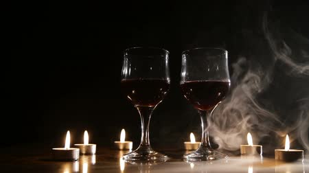 カベルネ : Two glasses of wine on black background and burning candles in the smoke..Glasses of red wine over candlelight and darkness.Romantic atmosphere with wine glasses and candles.