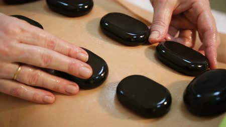 descontraído : Beautiful woman relaxing in spa salon with hot stones on body. Beauty treatment therapy.young woman receiving hot stone massage.Stone therapy,stone massage.Spa treatments, beauty center. In a the beauty salon.