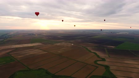 dirigível : Hot air balloons in the sky over a field in the countryside.Aerial view:Hot air balloons in the sky over a field in the countryside, beautiful sky and sunset.Aerostat fly the countryside. 4K video,ultra HD.