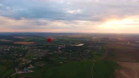 tej : Red balloon in the shape of a heart.Aerial view:Hot air balloon in the sky over a field in the countryside, beautiful sky and sunset.Aerostat fly in the countryside. 4K video,ultra HD. Stock mozgókép