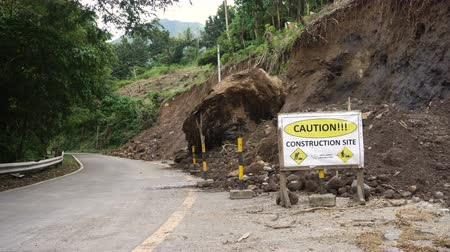 lebontották : Sign caution,construction site. Landslides and rockfalls on the road in the mountains. Mud and rocks blocking the road.Destroyed rural road landslide damaged in powerful flood. Collapsed on the mountain. Philippines, Camiguin. 4K video. Stock mozgókép