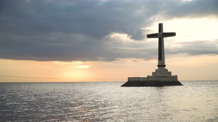 daan : Sunken Cemetery cross in Camiguin Island, Philippines. Large crucafix marking the underwater sunken cemetary of the coast of camiguin island near mindanao in the Philippines. Catholic cross in the water on the background of sky and clouds.. The Sunken Cem