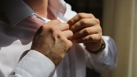 smokin : Man the groom fastens buttons on a shirt on a wedding day. Young handsome groom wears wedding shirt. Stok Video