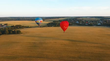 dirigível : Aerial view Hot air balloon in the sky over a field in the countryside in the beautiful sky and sunset.Aerostat fly in the countryside. Aerial footage, 4K
