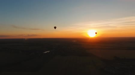 dirigível : Aerial view Hot air balloon in the sky over a field in the countryside in the beautiful sky and sunset. Balloon silhouette with sunrise, Aerostat fly in the countryside. Aerial footage, 4K
