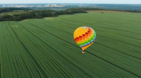 from air : Aerial view Hot air balloon in the sky over a field in the countryside. Aerostat fly in the countryside. Aerial footage, 4K