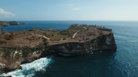 roccioso : Aerial view of Rocky coast with high cliffs, sea surf with breaking waves on the coast, Nusa Penida, Indonesia. Ocean with waves and rocky cliff. 4K video. Travel concept Aerial footage