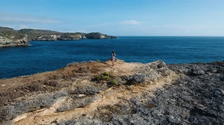 bali : Aerial view of young girl stands on the edge of a cliff and looks at the sea Nusa Penida. Girl raising her hands up on the edge of the cliff enjoys the view of the ocean. 4K video. Travel concept. Aerial footage. Stok Video