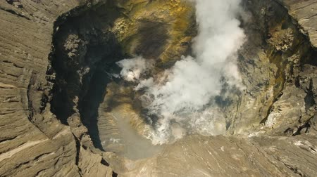cratere : Inside the active volcano crater, white smoke. Aerial view of volcano crater Mount Gunung Bromo is an active volcano,Tengger Semeru National Park. 4K video. Aerial footage. Filmati Stock