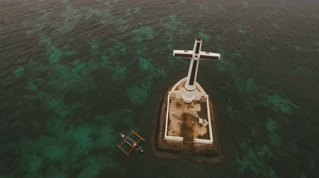 daan : Aerial view Sunken Cemetery cross in Camiguin Island, Philippines. Large crucafix marking the underwater sunken cemetary of the coast of camiguin island near mindanao in the Philippines. Catholic cross in the water. The Sunken Cemetery marks the swept rem
