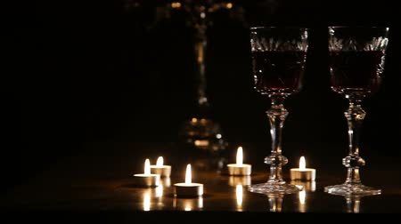 şarap kadehi : Two glasses of wine on black background and burning candles..Glasses of red wine over candlelight and darkness..Slider video footage.Romantic evening with wine. Stok Video