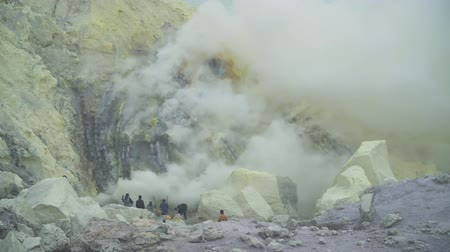 enxofre : Extraction of sulfur in the crater of a volcano. Sulfur, sulfur gas, smoke. Kawah Ijen, crater with acidic crater lake where sulfur is mined. Ijen volcano complex is a group of stratovolcanoes in the Banyuwangi Regency of East Java, Indonesia. Stock Footage