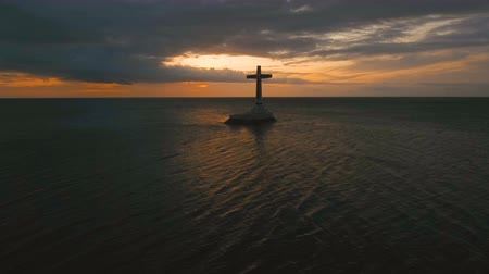mindanao : Aerial view Sunken Cemetery cross in Camiguin Island, Philippines,sunset. Large crucafix marking the underwater sunken cemetary of the coast of camiguin island near mindanao in the Philippines. Catholic cross in the water on the background of sky and clou Stock Footage