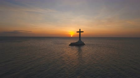 надгробная плита : Aerial view Sunken Cemetery cross at sunset in Camiguin Island, Philippines. Large crucafix marking the underwater sunken cemetary of the coast of camiguin island near mindanao in the Philippines. Catholic cross in the water on the background of sky and c