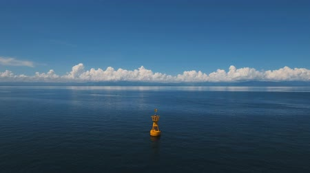 bója : Orange buoy in the blue sea on a background of blue sky, clouds, island. Aerial view:navigational buoy in the ocean.Philippines, Cebu. 4K video. Travel concept. Aerial footage. Stock mozgókép