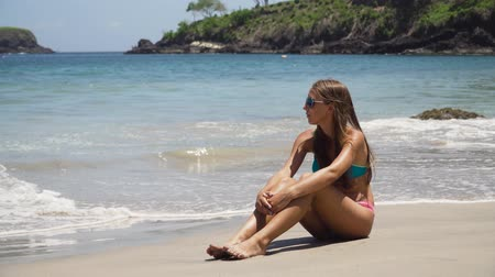 rozmazlování : Girl in the sun glasses sits on a sandy beach among the waves and looks at the sea.Young girl relaxing at Tropical Beach. Recreation and pampering on the seashore (ocean, river, lake) in summer and sunny day.