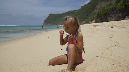 genç kız : Cute little girl is sitting on sandy beach near the sea and eating a lollipop on a warm summer day. Holiday on a seashore concept. Funny kids. Sea. Ocean.