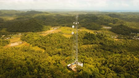 telephone tower : Communication tower, cellphone tower in the jungle in the mountains. Aerial view: satellite, cellphone tower, on a mountain. View of a tropical island with palm trees and other vegetation, a mountain and white telecom radio tower. 4K video. Aerial footage Stock Footage