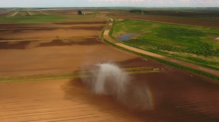 borrifador : Irrigation equipment watering freshly seeded field.Rainbow by irrigation.Irrigation of farmland to ensure the quality of the crop.Aerial view:irrigation system watering a farm field.