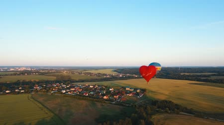 tej : Aerial view Hot air balloon shape of a heart in the sky over a field in the countryside, beautiful sky and sunset. Aerostat fly in the countryside.Aerial footage, 4K