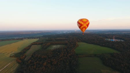 dirigível : Aerial view Hot air balloon in the sky over a field in the countryside in the beautiful sky and sunset. Aerostat fly in the countryside. Aerial footage, 4K