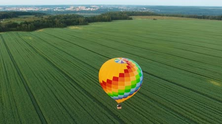 sıcak : Aerial view Hot air balloon in the sky over a field in the countryside. Aerostat fly in the countryside. Aerial footage, 4K