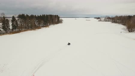 quadbike : ATV race on the snow. Aerial view: Rider driving in the quadbike race. Man riding ATV in sand in protective clothing and a helmet. Racer rides a quad motorbike in the cross racing. Quadrocycle on the snow cover. 4K video, drone footage.