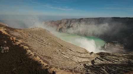 sulfur : Crater with acidic crater lake the famous tourist attraction, where sulfur is mined. Aerial view of Ijen volcano complex is a group of stratovolcanoes in the Banyuwangi Regency of East Java, Indonesia. 4K Aerial footage.