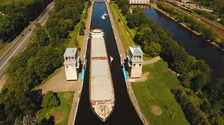 sluice : Sluice Gates on the River. Aerial view barge, ship in the river gateway. River sluice construction, water river gateway. Shipping channel. 4K, flying video, aerial footage Stock Footage