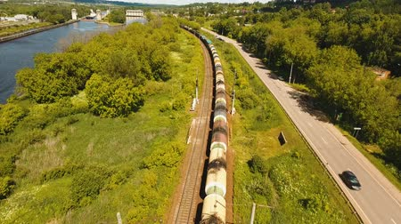 vagão : Freight train with cisterns and containers on the railway. Aerial view Container Freight Train, Locomotive in the countryside, Railway and highway. 4K, flying video, aerial footage.