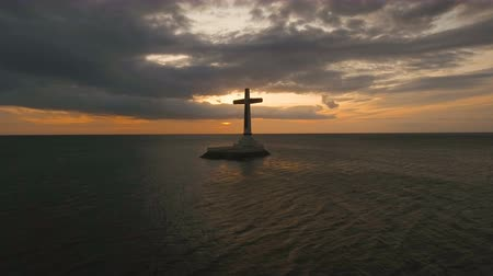 dark island : Aerial view Sunken Cemetery cross in Camiguin Island, Philippines,sunset. Large crucafix marking the underwater sunken cemetary of the coast of camiguin island near mindanao in the Philippines. Catholic cross in the water on the background of sky and clou Stock Footage