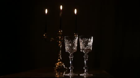 şarap kadehi : Two glasses and candle light at the restaurant.Two wine glasses,burning candles in a chandelier.Romantic atmosphere with wine glasses and candles. Stok Video