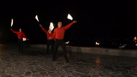 fişekçilik : Men artists twist fiery circles on a fire show.Men does a fire performance.Fire show amazing at night.