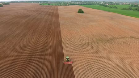 sowing : Aerial view of ploughed field with tractor sowing seeds of wheat. Industrial background on agricultural theme.Farm tractor and seeder planting crops on a field.Farm tractor handles field. Stock Footage