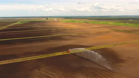 뿌리다 : Irrigation equipment watering freshly seeded field.Irrigation of farmland to ensure the quality of the crop.Aerial view:irrigation system watering a farm field.