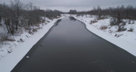 geada : Aerial view winter river with snow-covered shore. Flight over the river in winter in the countryside. Aerial footage.