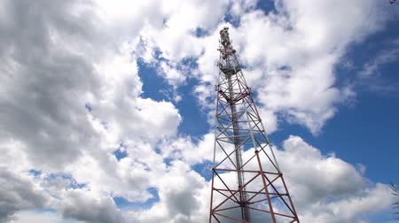 сталь : Cell phone tower against a blue sky. Tower of communications with a lot of different antennas under blue sky and clouds. Telecommunication tower with blue sky. 4K video