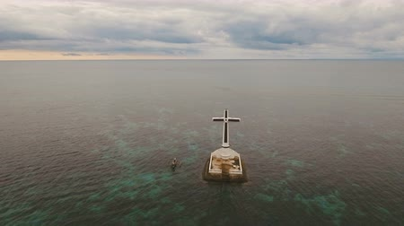 daan : Aerial view Sunken Cemetery cross in Camiguin Island, Philippines. Large crucafix marking the underwater sunken cemetary of the coast of camiguin island near mindanao in the Philippines. Catholic cross in the water on the background of sky and clouds.. Th Stock Footage