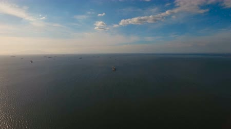 námořní : Aerial view Cargo ships in the Bay of Manila. Large container ship in the sea. Flying over the water surface of the sea with ships, blue sky and clouds. 4K video. Aerial footage. Philippines, Manila.