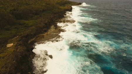 burza : Rocky coast line in time stormy weather on island Siargao. Aerial view sea rocky coast, waves breaking to the rocky shore. Rocky coastline. Big waves crushing on the shore. Philippines. 4K video. Travel concept. Aerial footage. Wideo