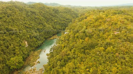 zip line : People have fun a zip line through a canyon with a river in the rainforest jungle. Aerial view, tourist attraction at the zipline attraction in the jungle on the island of Bohol. 4K video. Travel concept. Aerial footage. Stock Footage