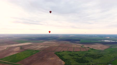 tej : Hot air balloons in the sky over a field in the countryside.Aerial view:Hot air balloons in the sky over a field the countryside in the beautiful sky and sunset.Aerostat fly over countryside. Stock mozgókép