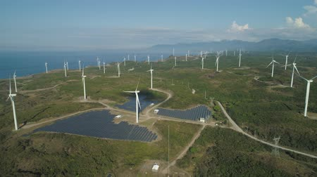 ecológico : Aerial view of Windmills for electric power production on the seashore. Bangui Windmills in Ilocos Norte, Philippines. Solar farm, Solar power station. Ecological landscape: Windmills, sea, mountains.Pagudpud.
