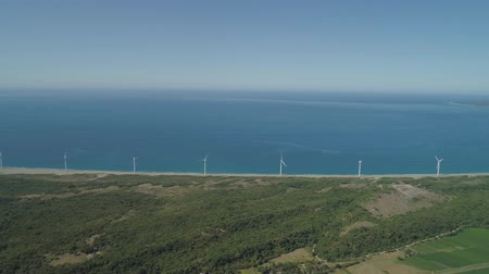 generaties : Luchtfoto van windmolens voor stroomproductie aan de kust. Bangui-windmolens in Ilocos Norte, Filippijnen. Ecologisch landschap: windmolens, zee in Pagudpud. Stockvideo