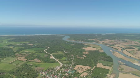 поток : River passing through farmlands and flowing into sea. Philippines, Luzon. Aerial view of river, agricultural land against blue sky.