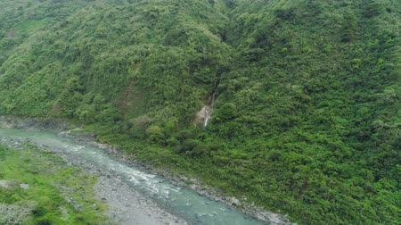 luzon : Aerial view of waterfall in the mountains of Filipino cordillera. Waterfall in the mountains. waterfall flowing on the slopes of mountains covered with tropical vegetation. Philippines, Luzon Stock Footage