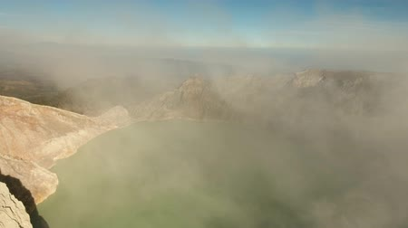 volkanik : Extraction of sulfur in the crater of a volcano. Sulfur, sulfur gas, smoke. Kawah Ijen, crater with acidic crater lake the famous tourist attraction, where sulfur is mined. Aerial view of Ijen volcano complex is a group of stratovolcanoes in the Banyuwang Stok Video