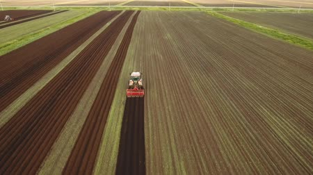 tırmık : Aerial view Farmer in tractor preparing land with seedbed cultivator in farmlands. Tractor plows a field. Agricultural work in processing, cultivation of land. Farmers preparing land and fertilizing. Agricultural workers with tractors. 4K, flying video, a